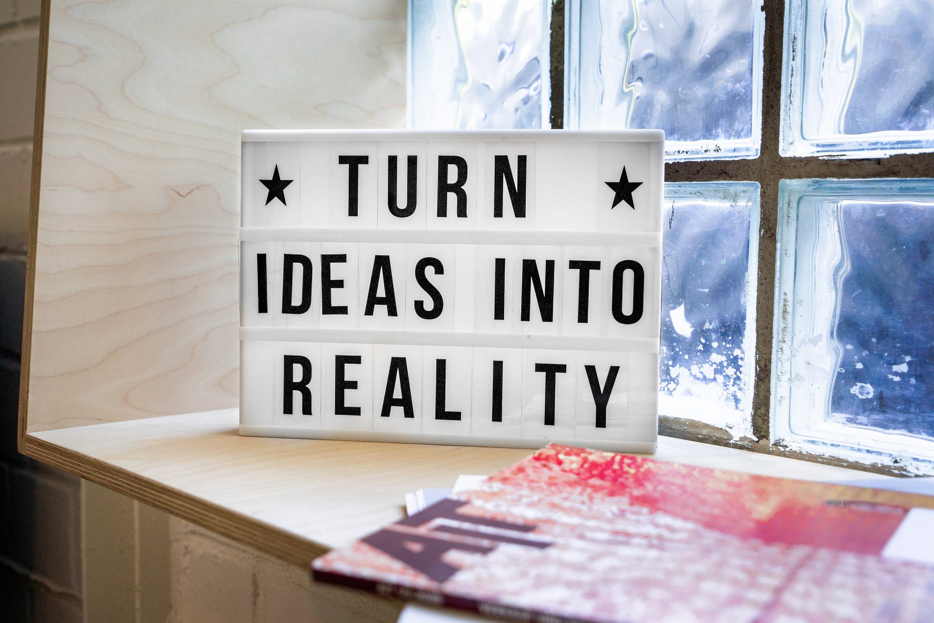 A light box on window sill showing turn ideas into reality