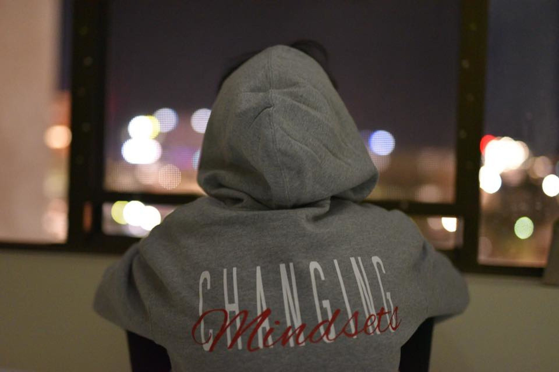 A girl sitting with her back to the camera with a hoodie stating Changing mindsets